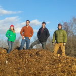 Farm staffers stand atop our leaf/compost pile.