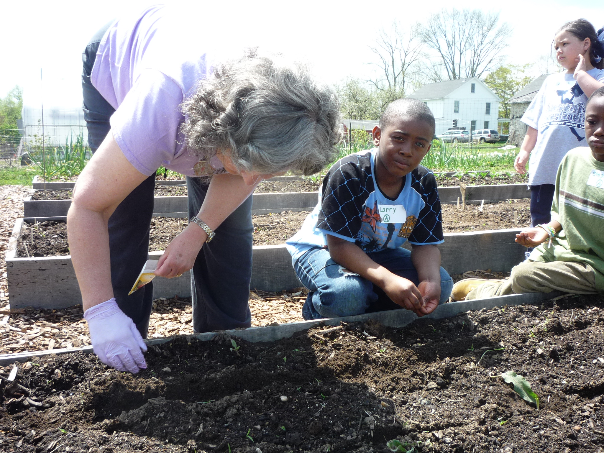 Education volunteer Emily Cosenza plants in the Learning Garden